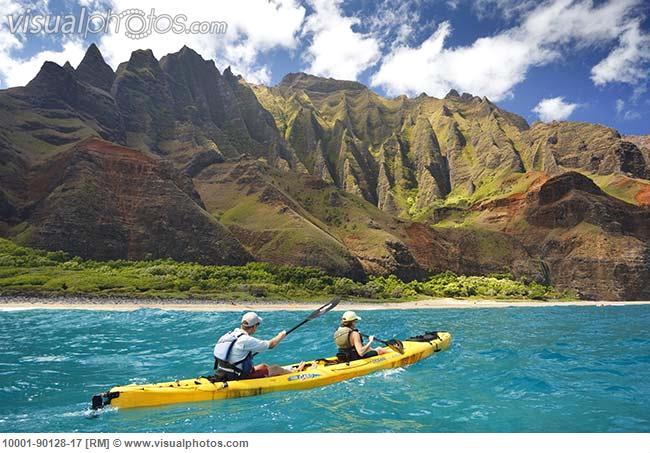 Hawaii, Kauai, Na Pali Coast, Couple kayaking along coastline, Beautiful mountain ridges in background. Editorial Use Only.